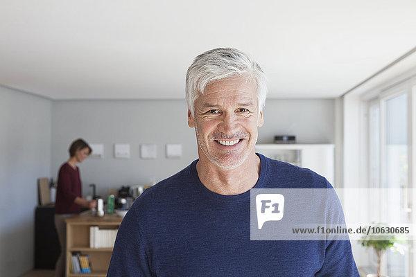 Porträt eines lächelnden Mannes mit grauen Haaren und Stoppeln zu Hause