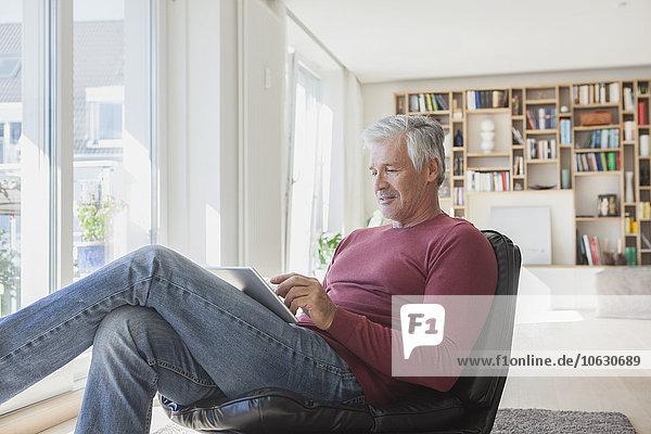 Der reife Mann entspannt sich zu Hause auf einem Ledersessel mit Hilfe eines digitalen Tabletts.