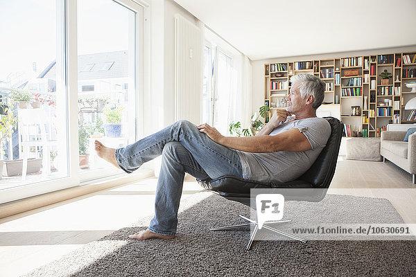 Nachdenklicher Mann  der sich zu Hause auf einem Ledersessel entspannt und durchs Fenster schaut
