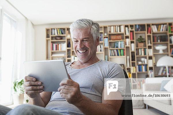 Porträt eines lachenden Mannes im Wohnzimmer mit Blick auf das digitale Tablett