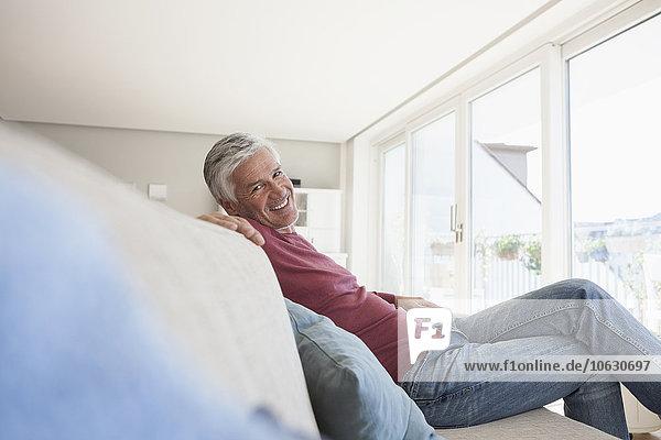 Porträt eines lächelnden Mannes  der zu Hause auf der Couch sitzt.