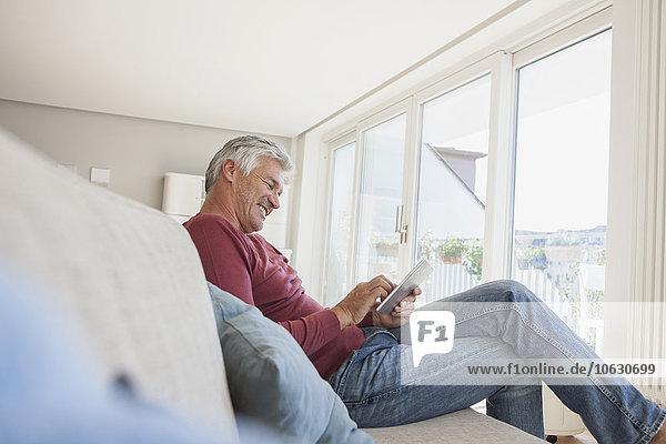 Lächelnder Mann sitzt zu Hause auf der Couch und benutzt ein digitales Tablett.