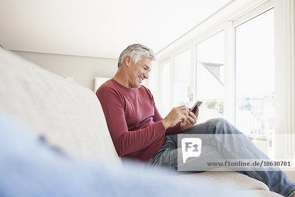 Lächelnder Mann auf der Couch zu Hause mit dem Smartphone