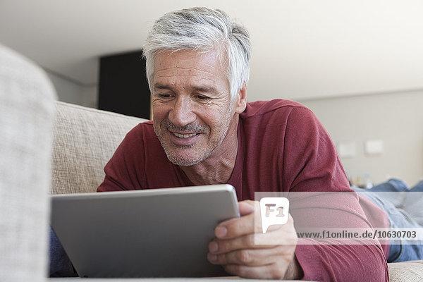 Porträt eines lächelnden Mannes  der zu Hause auf der Couch liegt  mit einem digitalen Tablett.