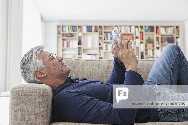 Erwachsener Mann  der zu Hause auf der Couch liegt und ein digitales Tablett benutzt.