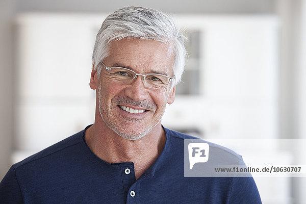 Porträt eines lächelnden reifen Mannes mit Stoppelbrille