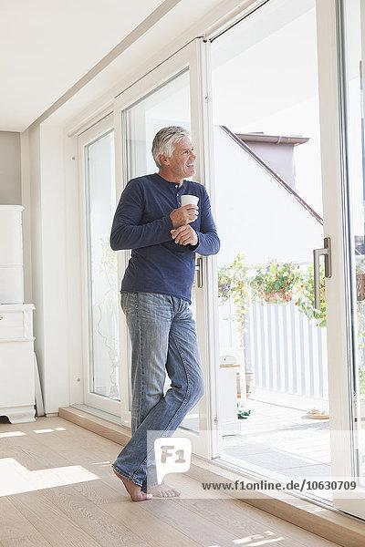 Lächelnder Mann  der sich gegen die Balkontür lehnt und in die Ferne schaut.