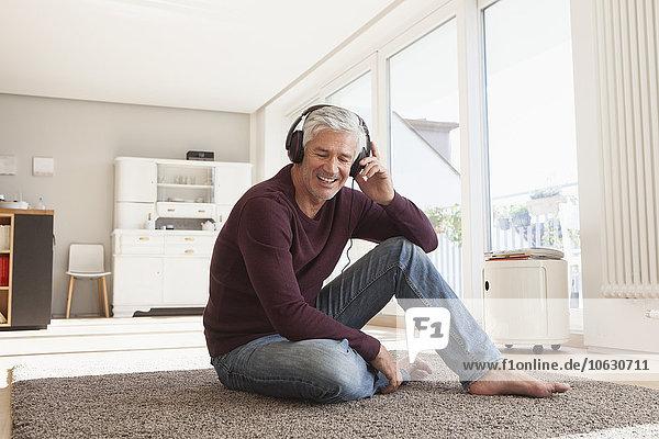 Porträt eines entspannten Mannes,  der zu Hause auf dem Boden sitzt und Musik mit Kopfhörern hört.