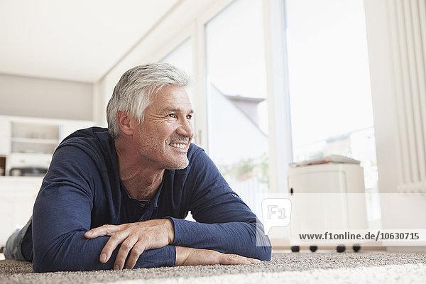 Lächelnder Mann zu Hause auf dem Boden liegend