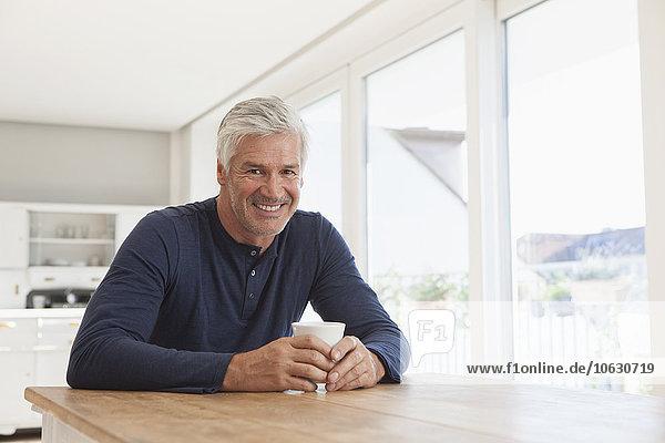 Porträt eines lächelnden reifen Mannes am Tisch mit einer Tasse Kaffee
