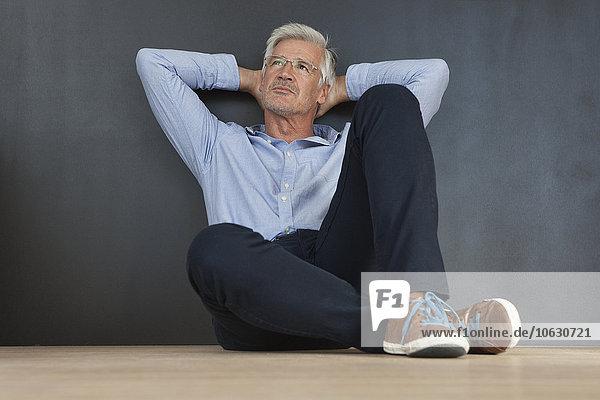 Porträt eines reifen Mannes mit den Händen hinter dem Kopf  der auf dem Boden vor einer grauen Wand sitzt.