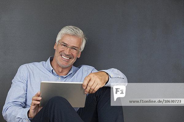 Porträt eines lächelnden reifen Mannes mit digitalem Tablett vor einer grauen Wand
