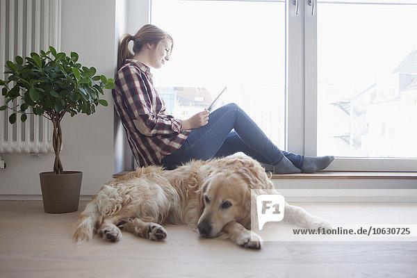 Junge Frau und ihr Hund entspannt zu Hause