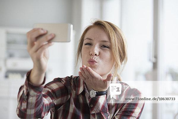 Junge Frau bläst einen Kuss  während sie einen Selfie mit ihrem Smartphone nimmt.