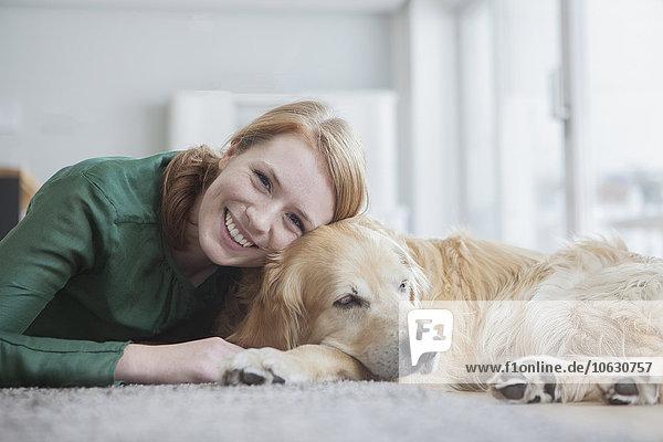 Porträt einer lächelnden jungen Frau  die mit ihrem Hund auf dem Teppich liegt.