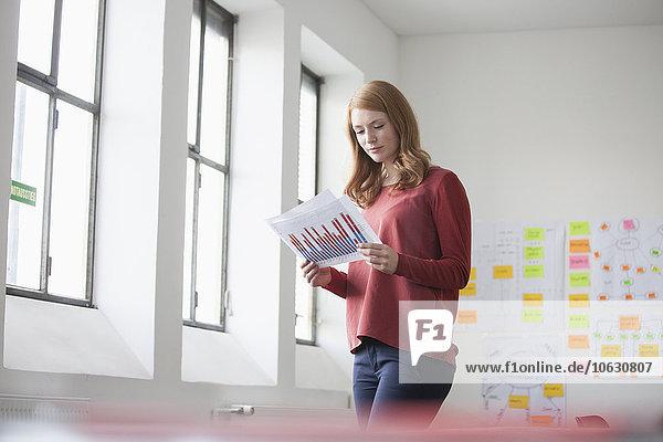Junge Frau in Büro-Lesekarten