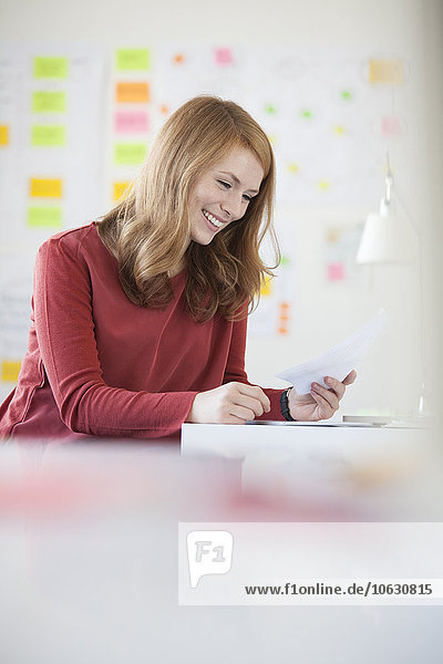 Junge Frau im Büro  die am Schreibtisch arbeitet