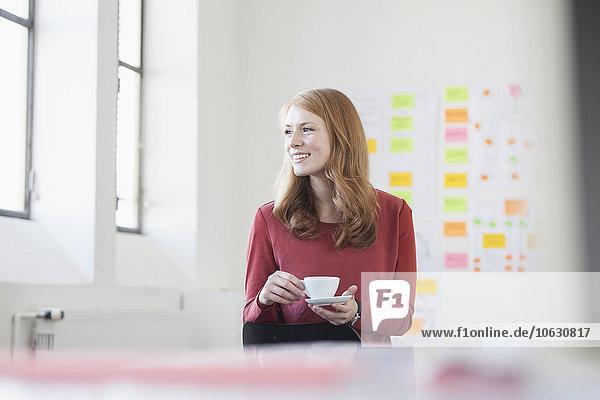 Junge Frau im Büro beim Kaffeetrinken