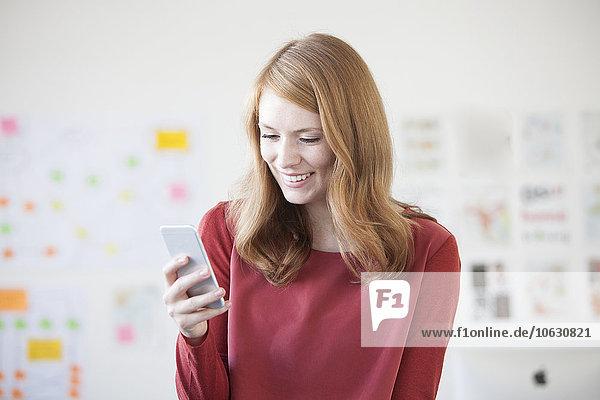 Junge Frau im Büro mit Smartphone