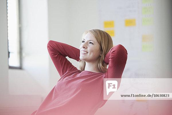 Junge Frau im Büro mit Händen hinter dem Kopf  Tagträumen