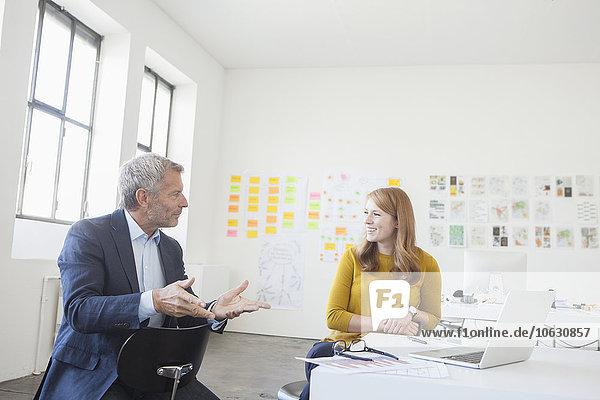 Geschäftsmann und Mitarbeiter diskutieren im Büro