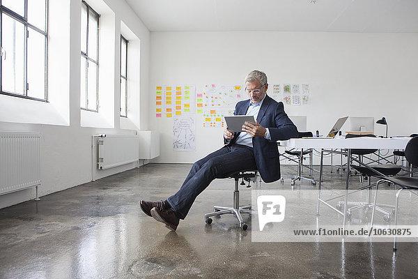 Erwachsener Geschäftsmann im Büro mit digitalem Tablett