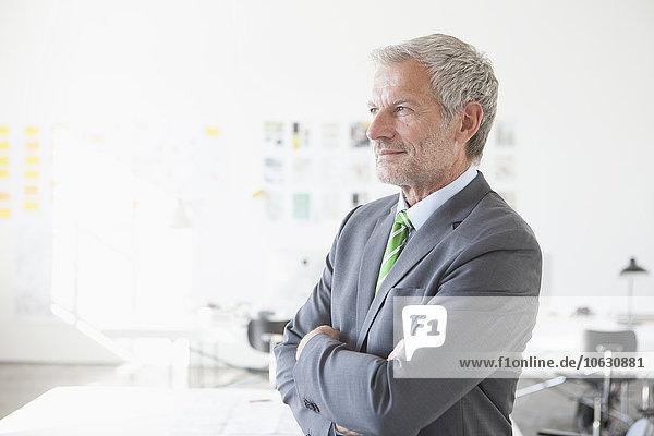 Zuversichtlicher Geschäftsmann im Bürodenken