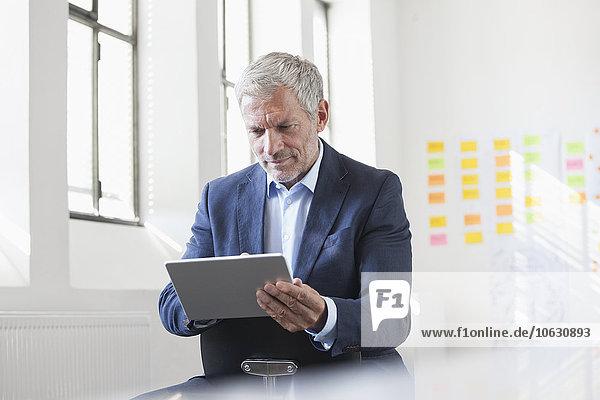 Geschäftsmann im Büro mit digitalem Tablett