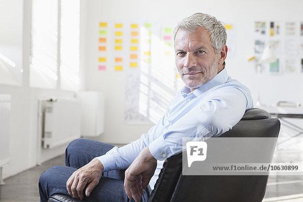 Zuversichtlicher Geschäftsmann auf dem Stuhl im Amt
