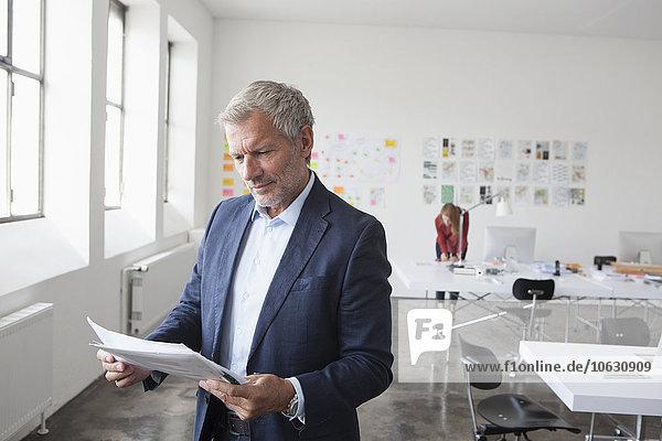Geschäftsmann im Büro auf der Suche nach Papier