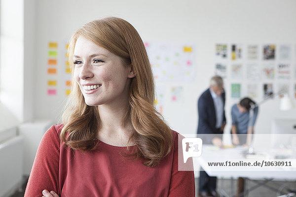 Lächelnde junge Frau im Büro schaut weg