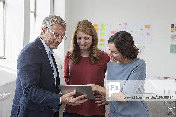 Lächelnder Usinessman und zwei Frauen im Büro beim Betrachten des digitalen Tabletts