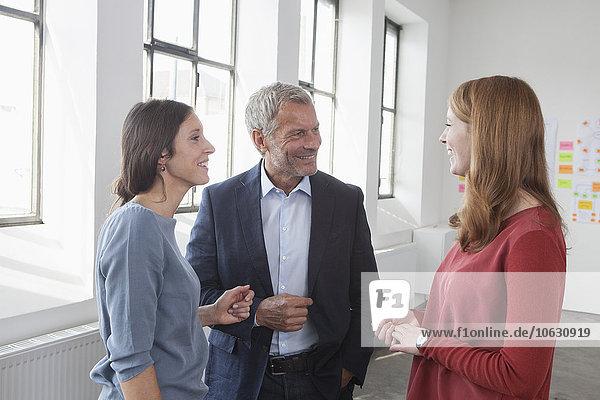 Lächelnder Geschäftsmann und zwei Frauen im Büro im Gespräch