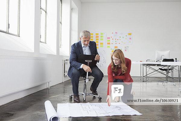 Geschäftsmann und Frau im Büro mit Blick auf den Bauplan