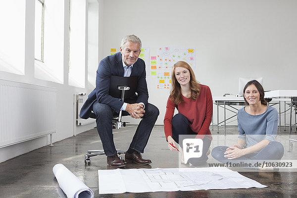 Porträt eines lächelnden Geschäftsmannes und zweier Frauen im Büro mit Bauplan
