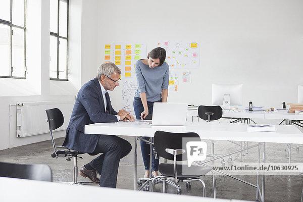 Geschäftsmann und zwei im Büro mit Blick auf Laptop