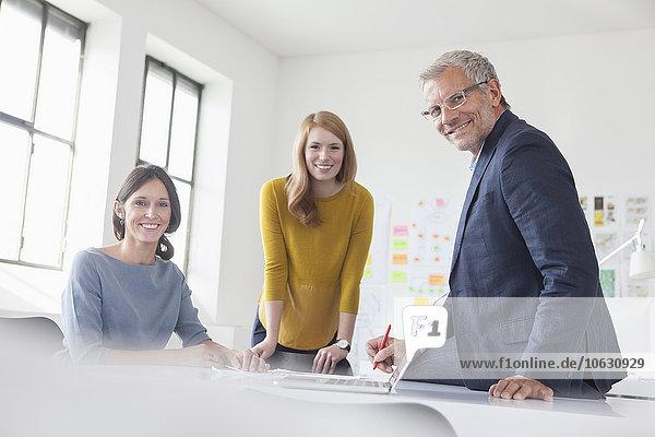 Porträt des lächelnden Geschäftsmannes und zweier Frauen im Amt