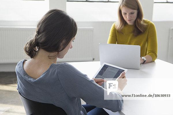 Zwei Frauen im Konferenzraum mit digitalem Tablett und Laptop