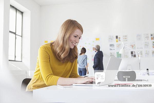 Lächelnde junge Frau im Büro am Schreibtisch mit Laptop