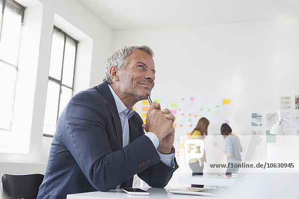 Lächelnder Geschäftsmann im Büro am Schreibtisch denkend
