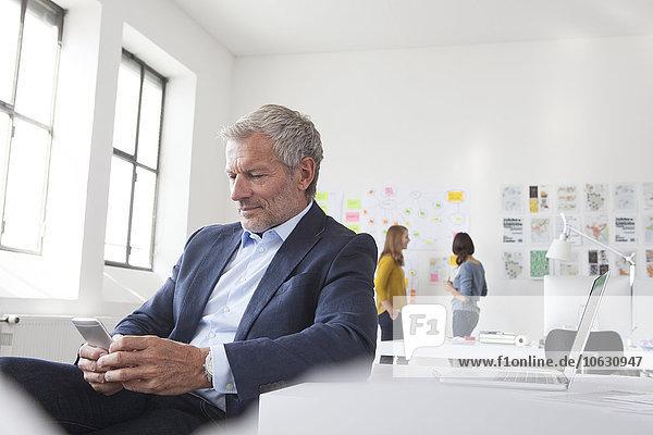 Geschäftsmann im Büro am Schreibtisch beim Blick aufs Handy