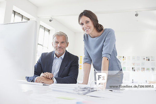 Porträt des lächelnden Geschäftsmannes und der Frau im Büro am Schreibtisch