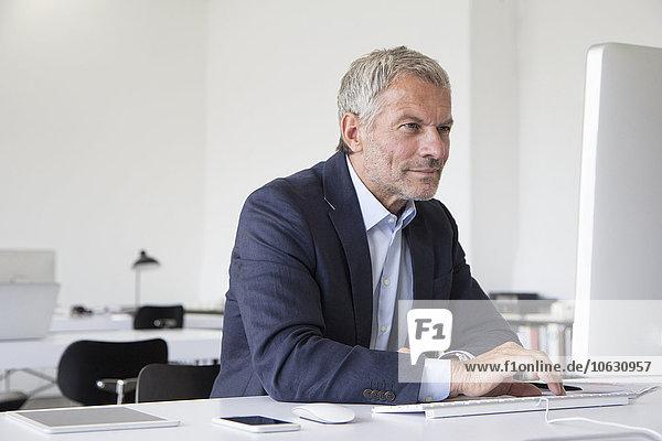 Geschäftsmann im Büro am Schreibtisch mit Computer