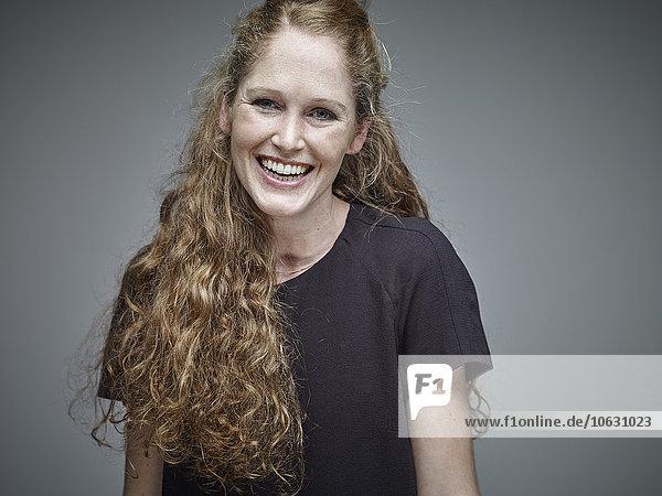 Porträt einer glücklichen jungen Frau mit langen blonden Haaren vor grauem Hintergrund