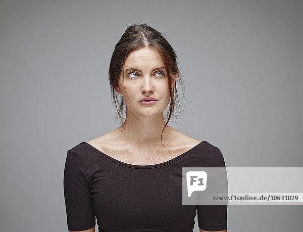 Porträt einer jungen Frau  die vor grauem Hintergrund aufblickt