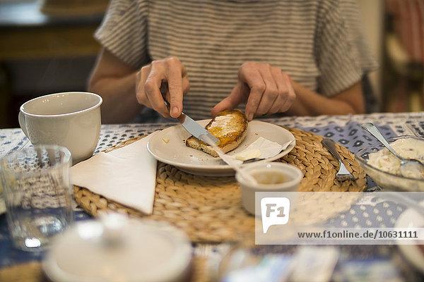 Frau streicht Brot mit Marmelade