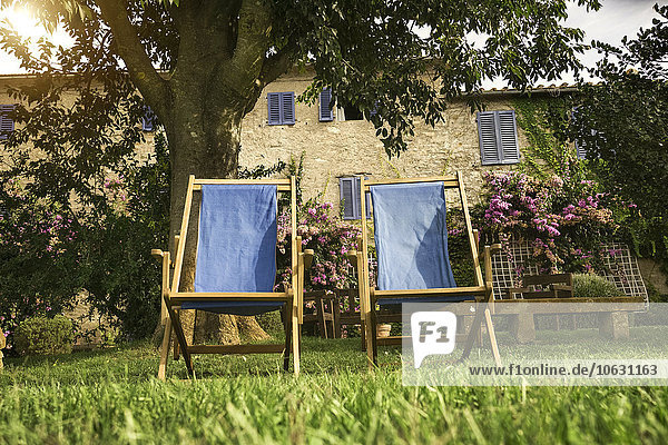 Italien  Toskana  Maremma  Liegestühle im blühenden Garten eines Landhauses