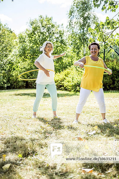 Happy mature women practising with hula hoops on meadow