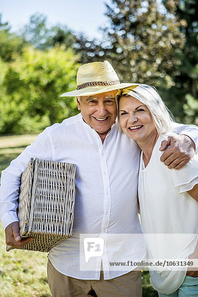 Porträt eines lächelnden älteren Paares mit Picknickkorb