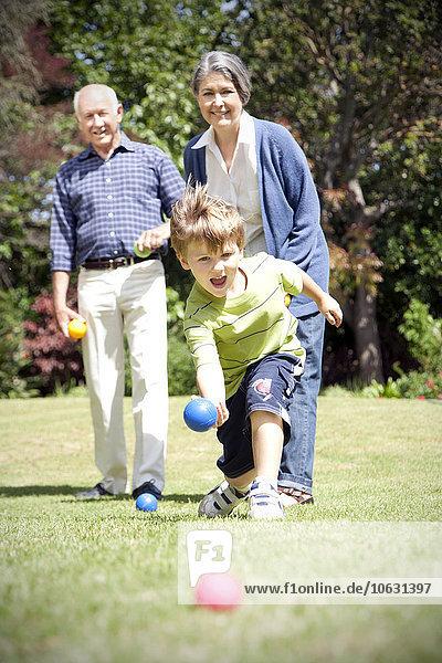 Kleiner Junge spielt Boccia mit seinen Großeltern Kleiner Junge spielt Boccia mit seinen Großeltern